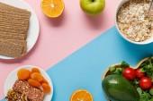 """Постер, картина, фотообои """"верхний вид вкусной диетической еды и спортивного оборудования на синем и розовом фоне с копировальной копией"""""""