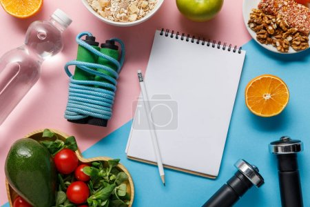 Photo for Top view of empty notebook and pencil with delicious diet food, water and sport equipment on blue and pink background - Royalty Free Image