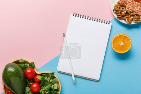 Photo for Top view of empty notebook, vegetable salad, orange and nuts on pink and blue background - Royalty Free Image