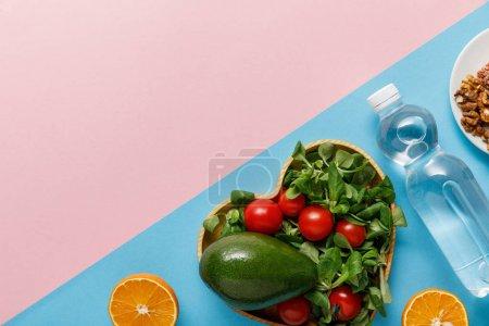 Photo pour Plat avec salade de légumes, oranges, eau et noix sur fond rose et bleu - image libre de droit