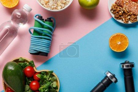 Photo pour Vue supérieure de la nourriture de régime, de l'eau, de la corde à sauter et des haltères sur le fond rose et bleu - image libre de droit