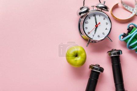 Foto de Vista superior de la manzana verde fresca, mancuernas, cinta de medición, saltar la cuerda y el reloj despertador en el fondo rosa con espacio de copia - Imagen libre de derechos