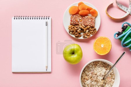 Photo for Top view of fresh diet food, measuring tape, skipping rope and blank notebook on pink background with copy space - Royalty Free Image