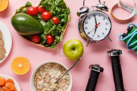 Photo for Top view of fresh diet food, measuring tape, sport equipment and alarm clock on pink background with copy space - Royalty Free Image