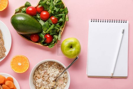 Photo for Top view of fresh diet food and blank notebook on pink background - Royalty Free Image
