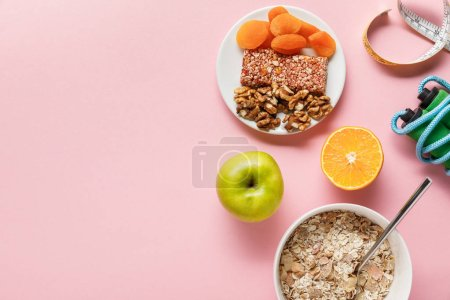 Photo for Top view of fresh diet food, measuring tape, skipping rope on pink background with copy space - Royalty Free Image