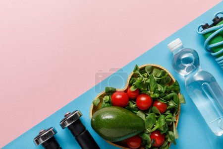 Photo for Flat lay with vegetable salad in heart-shaped bowl, water, skipping rope and dumbbells on pink and blue background - Royalty Free Image