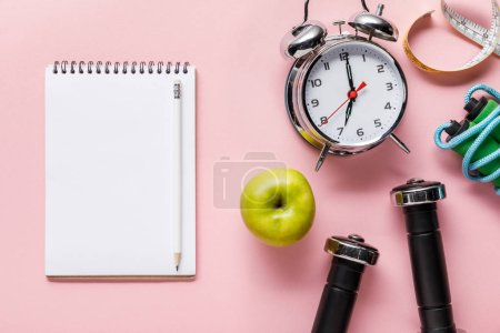 Photo for Top view of blank notebook, fresh green apple, dumbbells, measuring tape, skipping rope and alarm clock on pink background with copy space - Royalty Free Image