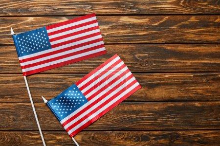 Photo pour Vue de dessus des drapeaux américains sur la surface en bois avec espace de copie - image libre de droit