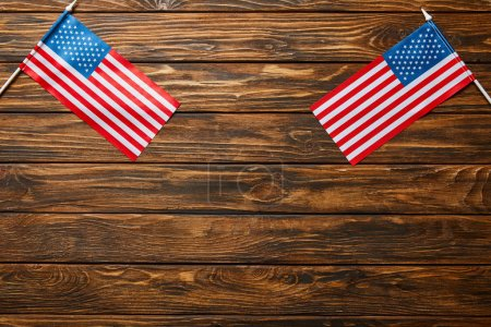 Photo for Top view of american flags on wooden brown surface with copy space - Royalty Free Image