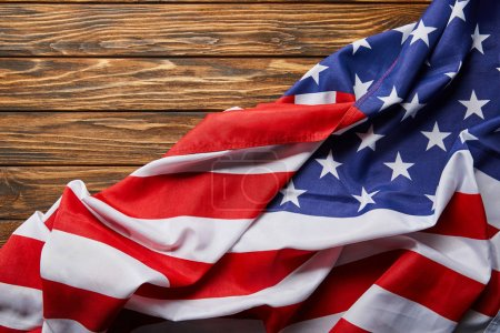 top view of usa flag on wooden textured surface with copy space