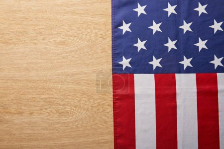 top view of national american flag on beige wooden surface with copy space