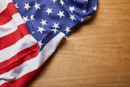 top view of american flag on light wooden surface