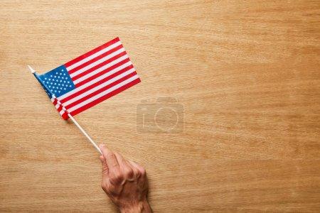 Photo pour Vue recadrée de l'homme retenant le drapeau américain sur le fond en bois avec l'espace de copie - image libre de droit
