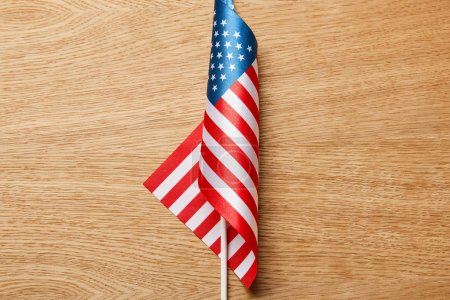 Photo for Top view of american flag on stick on wooden surface - Royalty Free Image