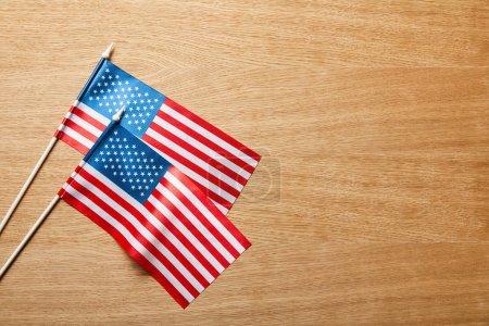 Photo pour Vue de dessus des drapeaux américains sur les bâtons sur la surface en bois avec espace de copie - image libre de droit