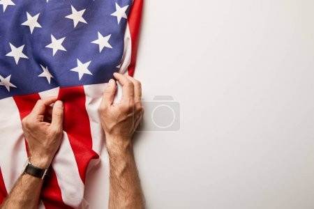 Photo pour Cropped view of man holding american flag on white background with copy space - image libre de droit