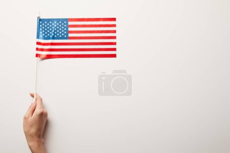 Photo for Partial view of woman holding american flag on white background with copy space - Royalty Free Image