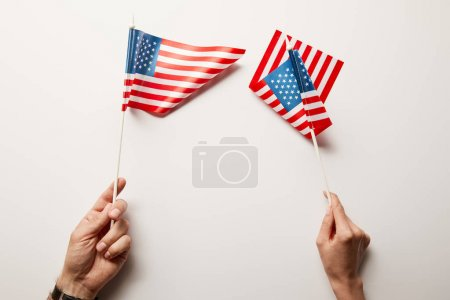 Photo pour Cropped view of woman and man holding american flags on white background - image libre de droit