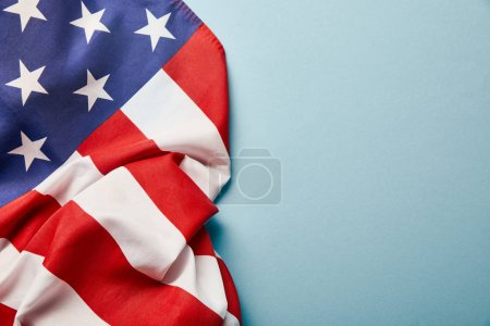 Photo pour Top view of crumpled american flag on blue background with copy space - image libre de droit