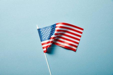 Photo pour Vue supérieure du drapeau américain sur le bâton sur le fond bleu - image libre de droit