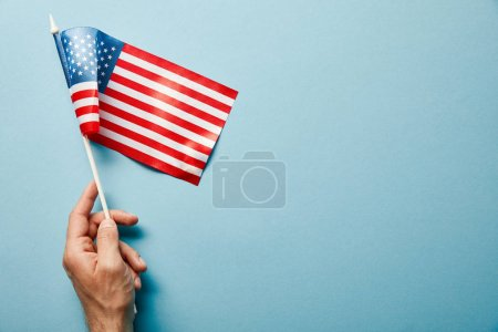 cropped view of man holding american flag on stick on blue background with copy space