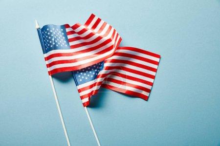 Photo pour Vue supérieure des drapeaux américains sur des bâtons sur le fond bleu - image libre de droit