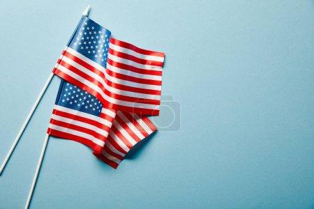 Photo pour Vue supérieure des drapeaux américains nationaux sur le fond bleu avec l'espace de copie - image libre de droit
