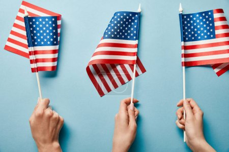 Photo for Cropped view of people holding american flags on blue background - Royalty Free Image