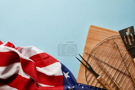 Photo for Top view of american flag near bbq equipment on blue background with copy space - Royalty Free Image
