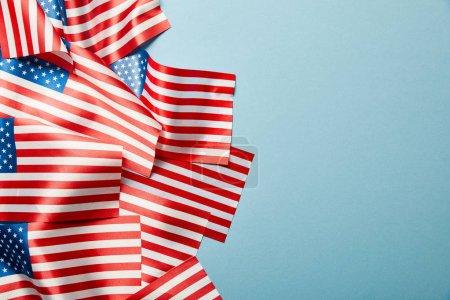 Photo pour Vue supérieure du tas des drapeaux américains sur des bâtons fond bleu avec l'espace de copie - image libre de droit