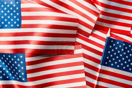close up view of shiny satin american flags in pile