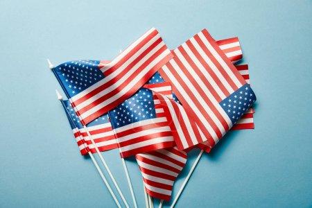 Photo pour Vue supérieure des drapeaux américains empilés sur le fond bleu - image libre de droit
