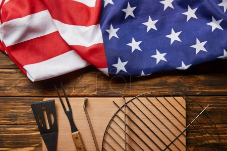 Photo for Top view of crumpled american flag and bbq equipment on wooden rustic table - Royalty Free Image