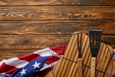 Foto de Top view of crumpled american flag and bbq equipment on wooden rustic table with copy space - Imagen libre de derechos