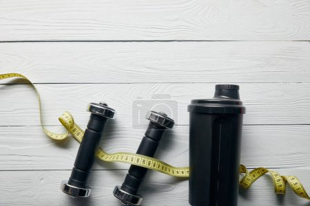 Photo for Top view of black shaker cup, measuring tape and dumbbells on wooden white background with copy space - Royalty Free Image