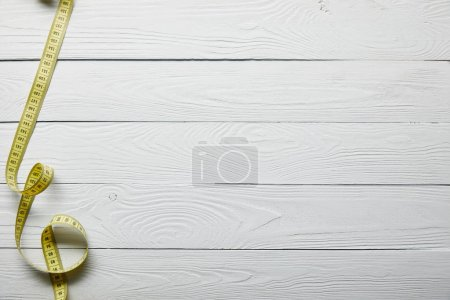 Photo for Top view yellow measuring tape on wooden white surface with copy space - Royalty Free Image