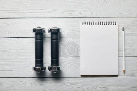 Photo pour Pose plate avec haltères, bloc-notes vierge avec espace de copie et crayon sur fond blanc en bois - image libre de droit