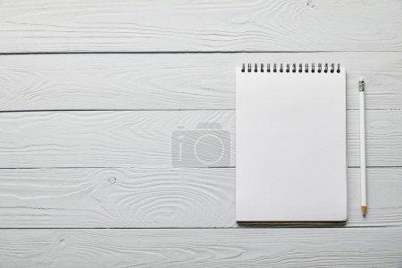 Photo pour Plat couché avec bloc-notes vierge avec espace de copie et crayon sur fond blanc en bois - image libre de droit
