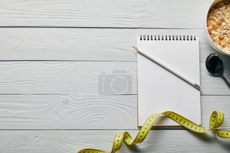 Photo for Top view of measuring tape, blank notebook, pencil, spoon and breakfast cereal in bowl on wooden white background - Royalty Free Image