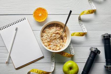 Photo for Top view of measuring tape, spoon and breakfast cereal in bowl near apple, orange, notebook, dumbbells and pencil on wooden white background - Royalty Free Image