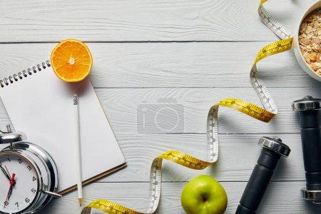 Photo pour Vue supérieure du ruban à mesurer, céréale de petit déjeuner dans le bol près de la pomme, orange, cahier, haltères, réveil et crayon sur le fond blanc en bois avec l'espace de copie - image libre de droit