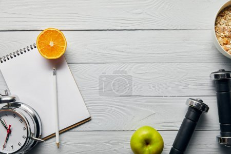 Photo for Top view of breakfast cereal in bowl near apple, orange, notebook, dumbbells, alarm clock and pencil on wooden white background with copy space - Royalty Free Image