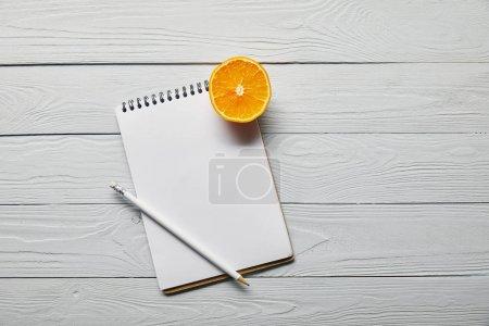 Photo pour Vue du haut de la moitié orange, carnet vierge et crayon sur fond blanc en bois avec espace de copie - image libre de droit