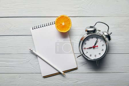 top view of orange half, blank notebook and pencil near alarm clock on wooden white background