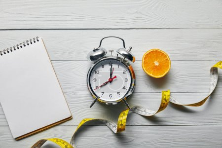 top view of orange half, blank notebook and measuring tape near alarm clock on wooden white background
