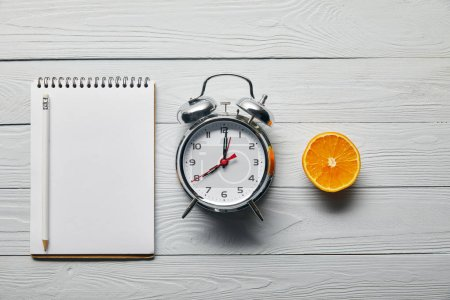 flat lay with silver alarm clock, empty notebook with pencil and orange half on wooden white background