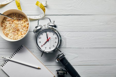 Photo for Top view of silver alarm clock, notebook with pencil, breakfast cereal, measuring tape, dumbbells on wooden white background with copy space - Royalty Free Image
