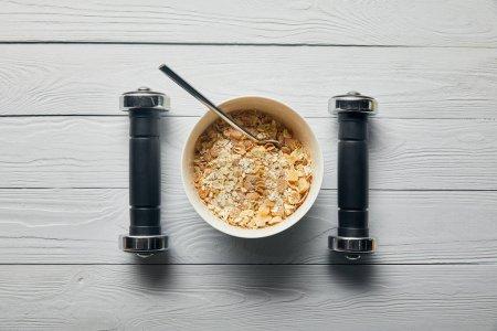 Photo pour Plat étendu avec céréales pour petit déjeuner dans un bol et haltères sur fond blanc en bois - image libre de droit