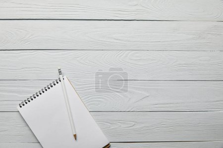 Photo for Top view of blank notebook with pencil on wooden white background with copy space - Royalty Free Image